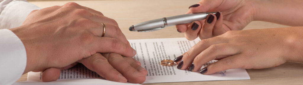 Hands of wife and husband signing divorce documents at their divorce lawyer in London