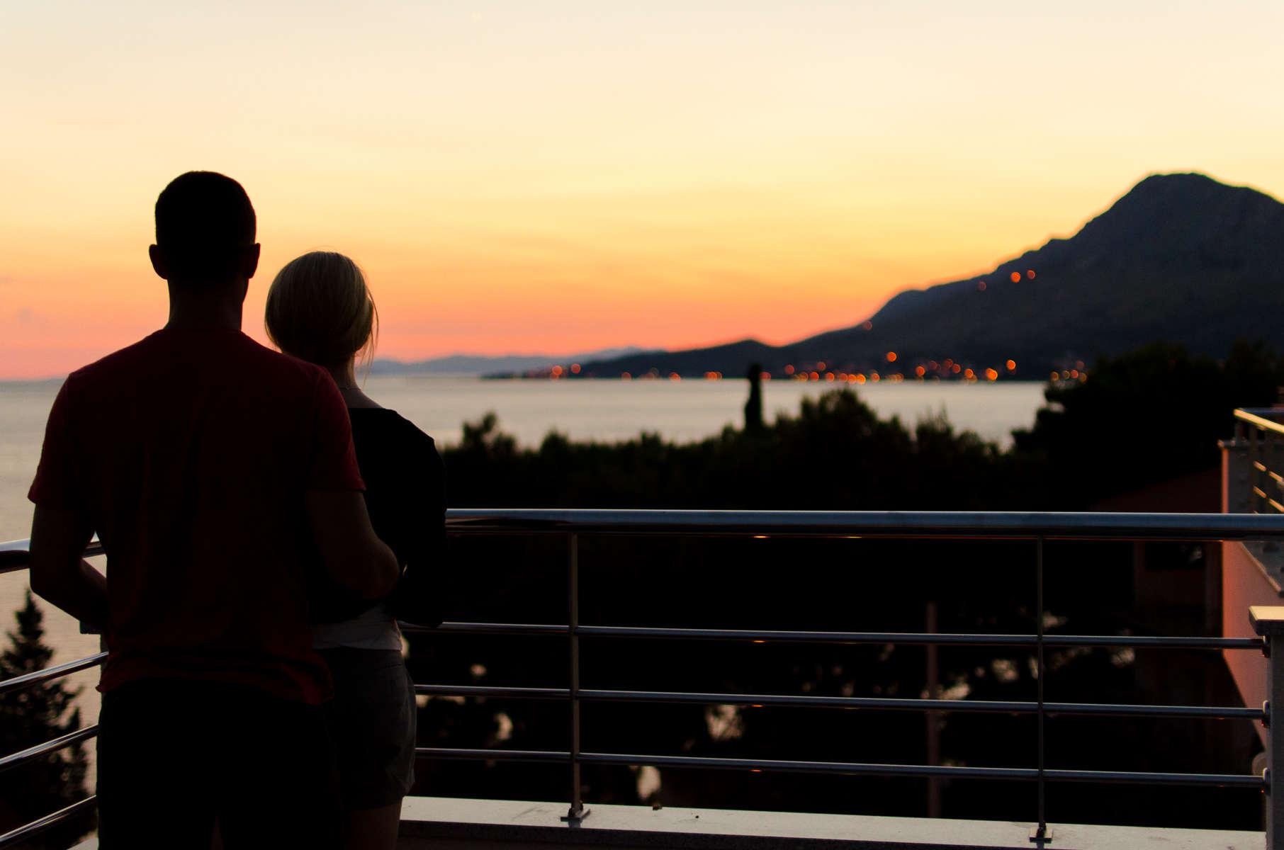 Couple stood on their balcony - KMJ family lawyers in London