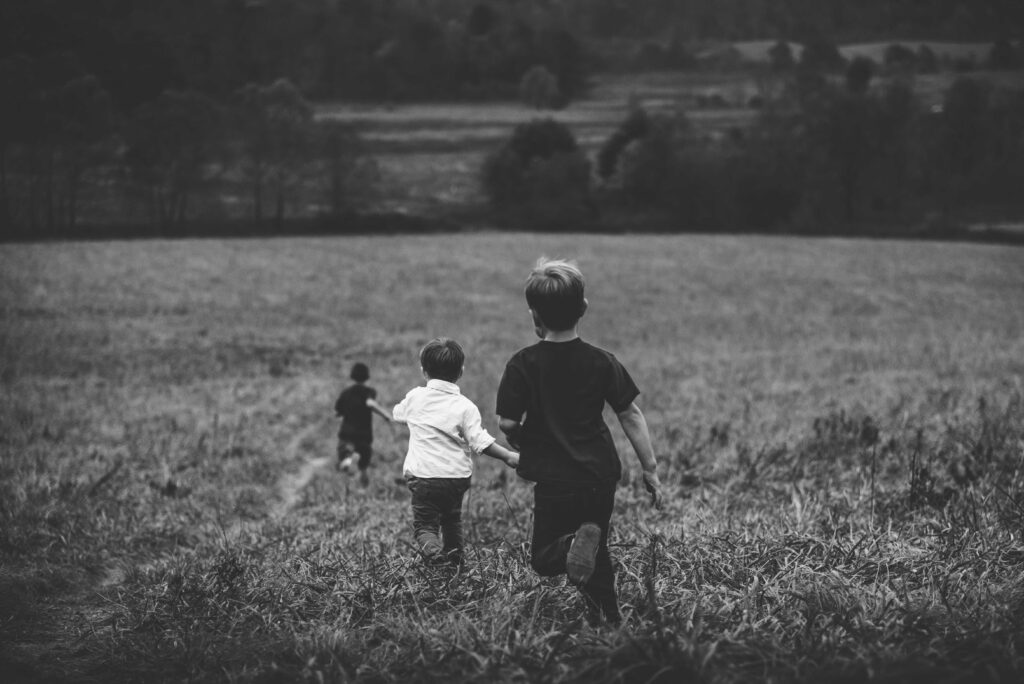 Children running in a field - KMJ family law solicitors in london