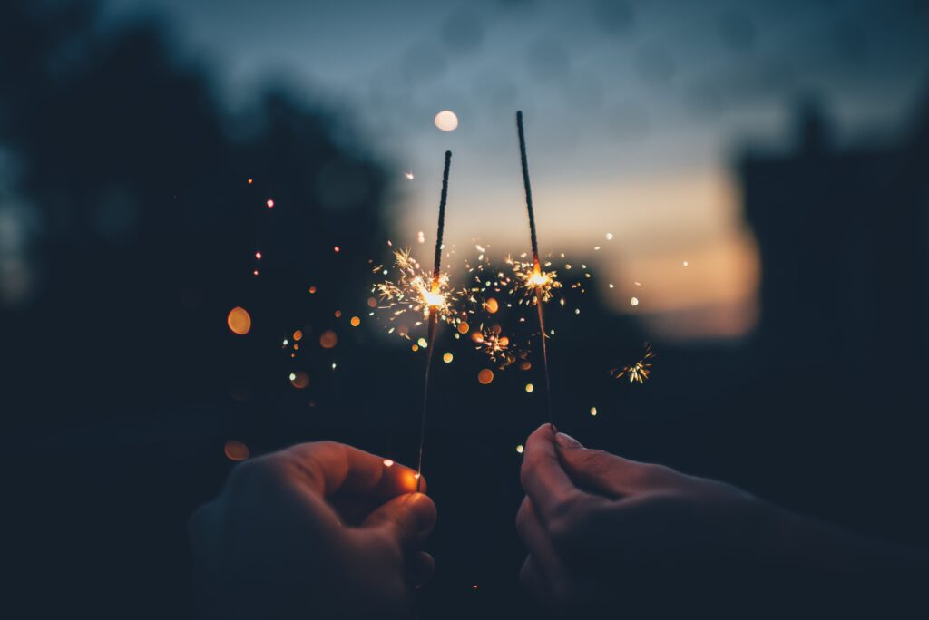 Two hands holding sparklers celebrating their new years resolutions from our divorce solicitors