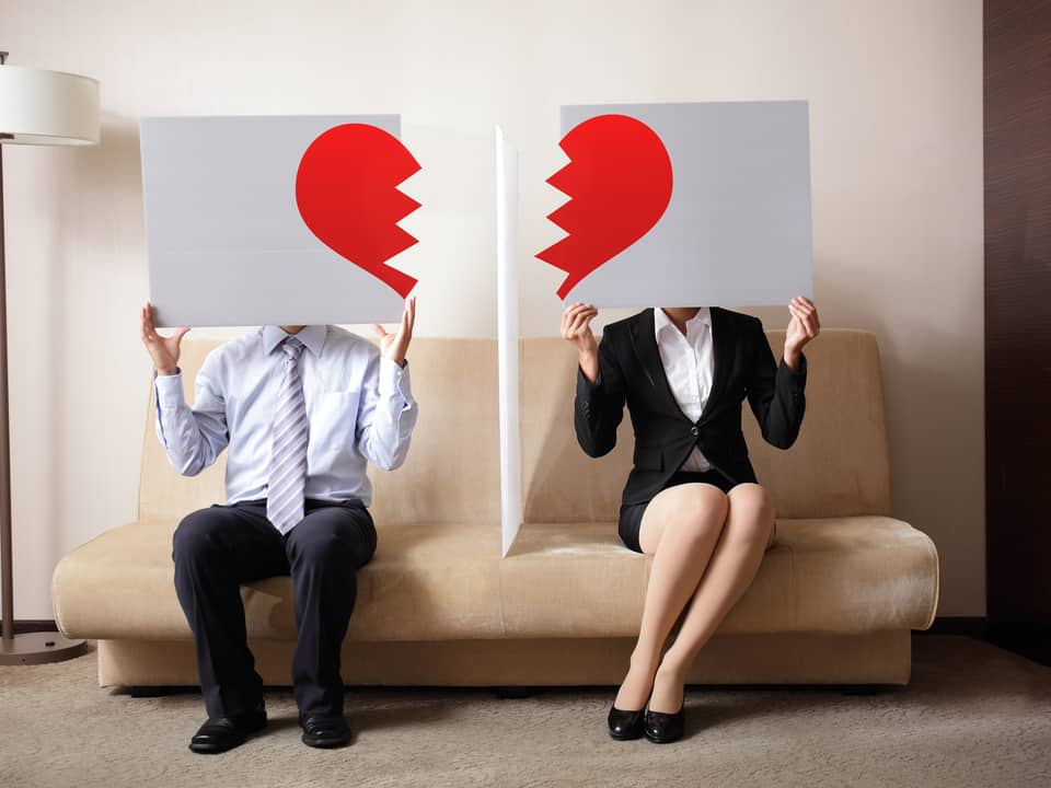 picture of a Couple holding broken heart posters seeking London Divorce Solicitors advice