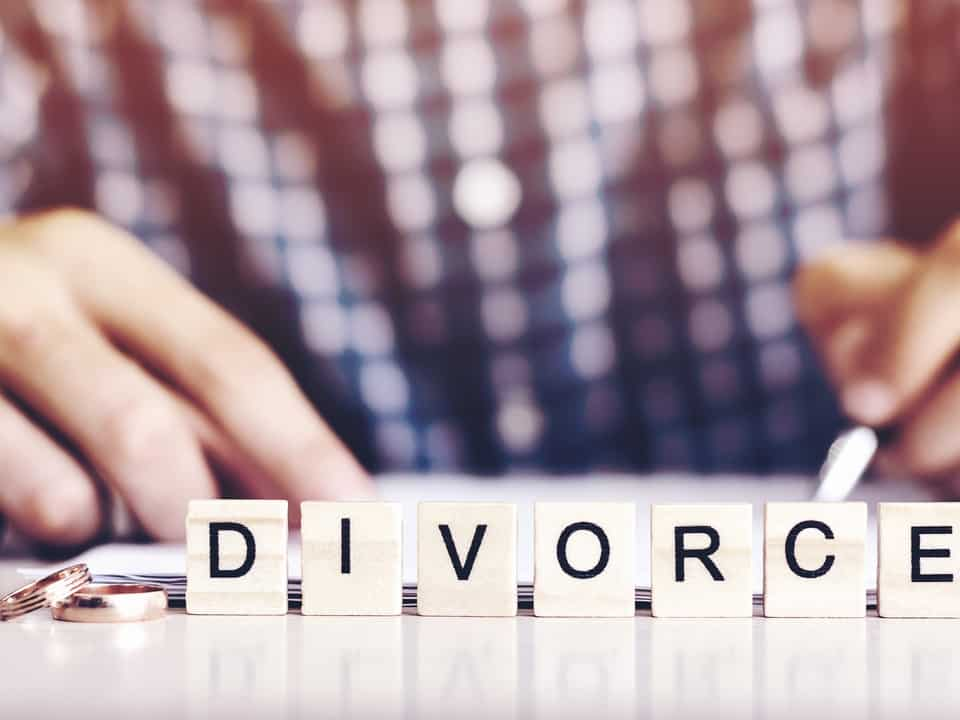 A man's hands with the word divorce spelt out in front of him on a desk with scrabble tiles