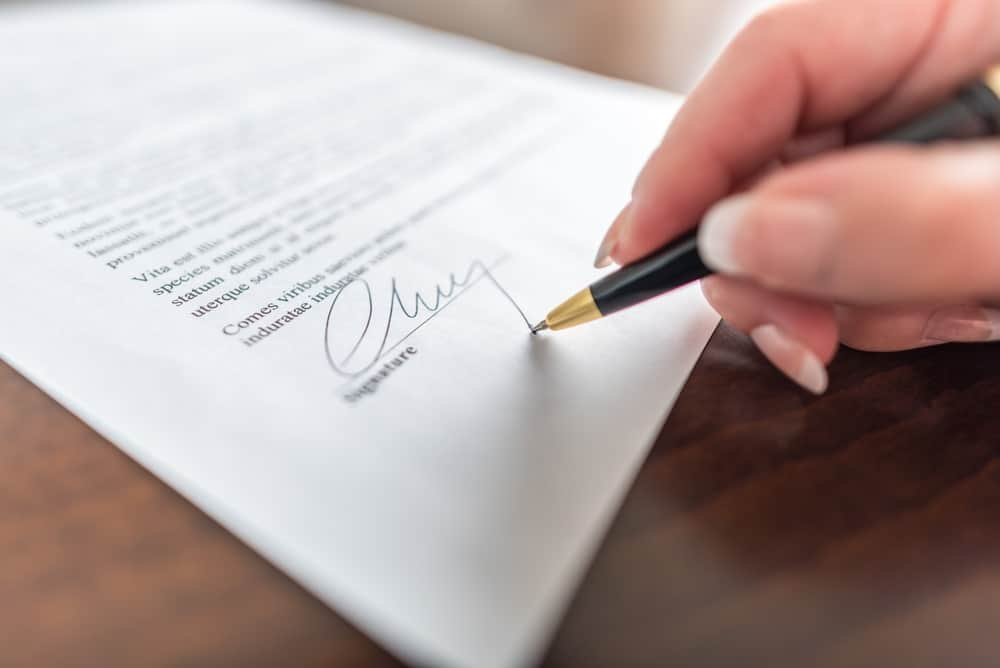 womans hand signing a prenuptial agreement