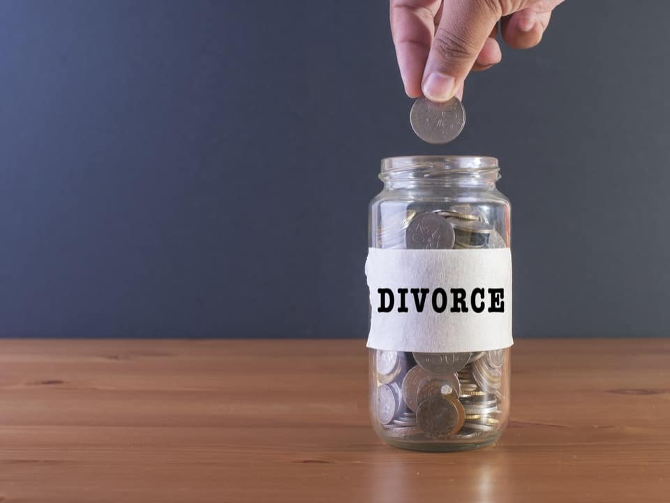 A hand putting a coin into a jar filled with money with the words divorce on it signifying the cost of divorce