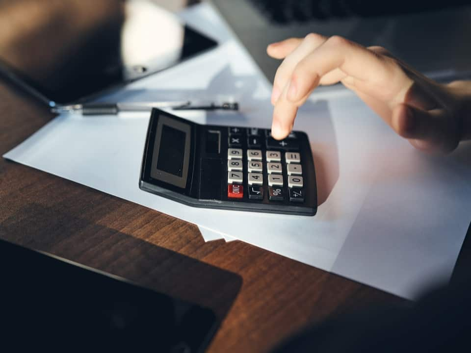 A female hand using a calculator working out the cost of a divorce financial settlement