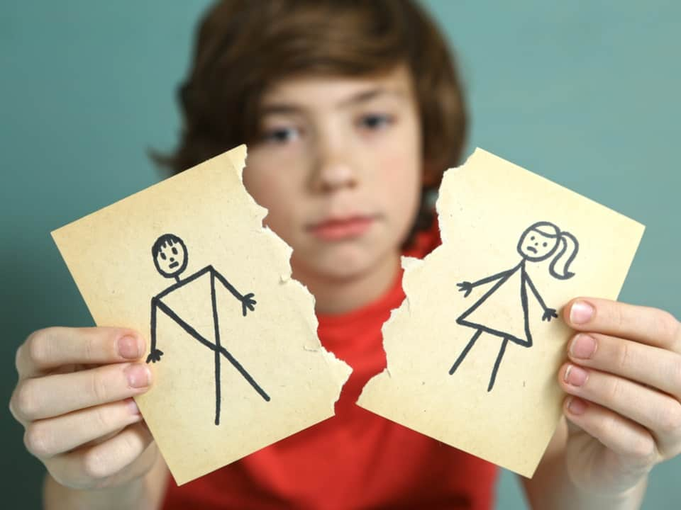 A child holding stick figure drawings of a male and female torn down the middle showing the impact of divorce and parental alienation on children