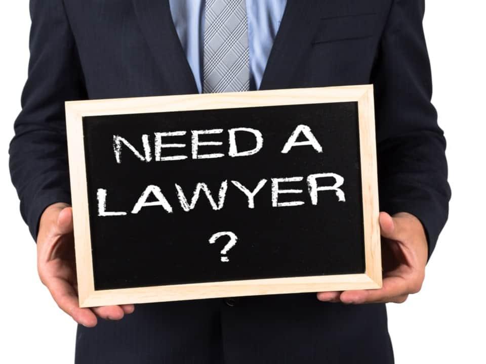 Man in suit holding a blackboard with need a lawyer written in chalk on it