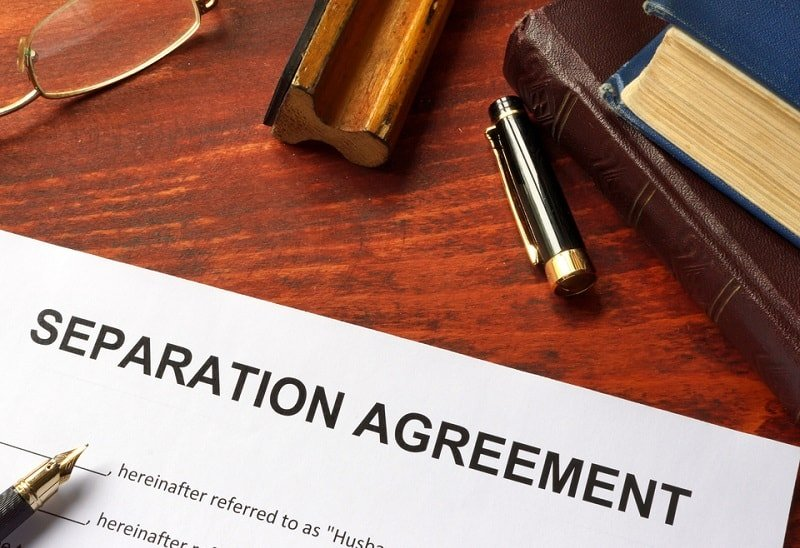 a close up of a separation agreement on a desk with a pen to sign it