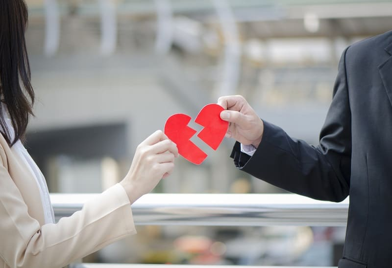 Male and female holding either side of a broken heart symbolising relationship breakdown and possible legal separation or divorce