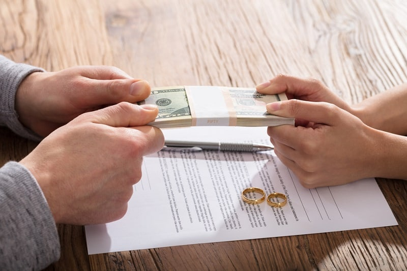 Couple's Fighting For Money Over The Legal Separation or Divorce Agreement With Gold Wedding Rings