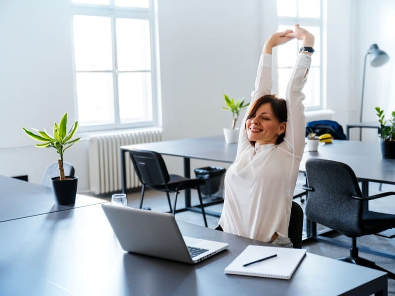 A relaxed divorced woman stretching her arms whilst working on a laptop symbolising how divorce can be good for your health and wellbeing