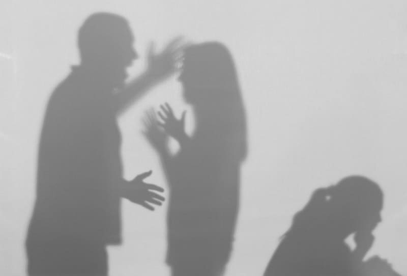 Silhouettes of quarrelling parents and little child on white background. Divorce with domestic violence concept