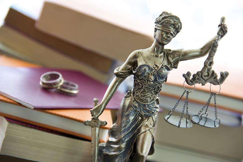 Family and divorce law in England and Wales. Justice statue with sword and scale and marriage certificate