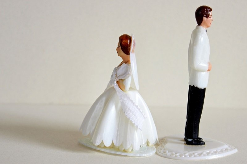 Bride and groom figures standing back to back symbolising breakdown of marriage, annulment and divorce