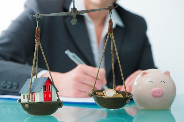 division of assets in divorce concept with house and cash money on scale.