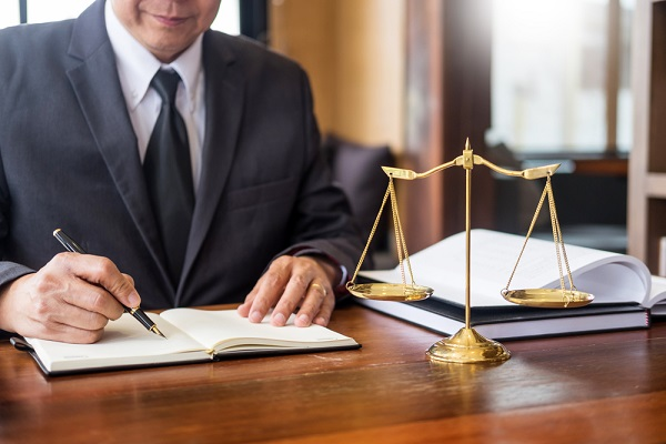 a private solicitor working for a client with gavel and document on wood table.