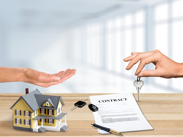 two hands with various marital assets around them, inc model home, car keys - symbolic of how to protect your assets during divorce.